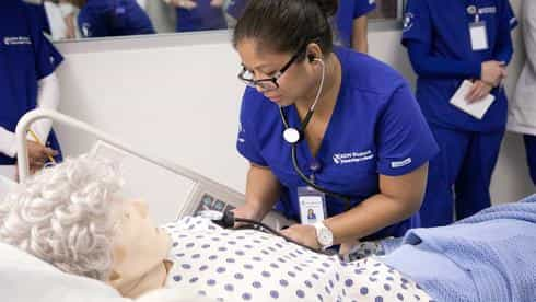Nursing students practice patient care in small groups with guidance from their instructor in the Nursing Simulation Lab.