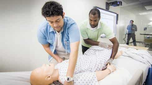 Students practice client care on a high-fidelity human simulator as an instructor provides them with real-time feedback by speaking through the manikin.